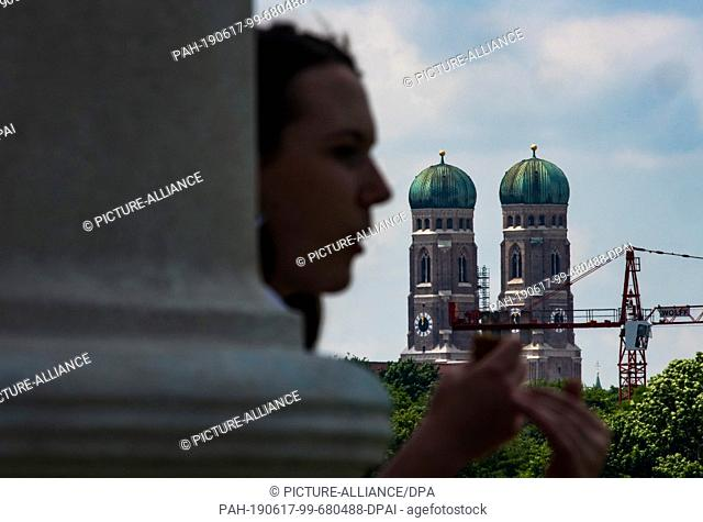 17 June 2019, Bavaria, Munich: The two towers of the Frauenkirche tower above the trees of the English Garden. In the foreground a woman sits on the steps of...