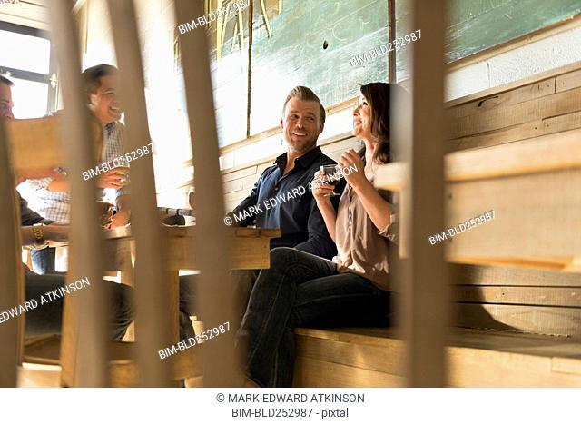 Friends talking in brew pub behind chair