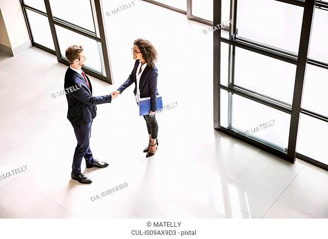 High angle view of businesswoman and man shaking hands at office entrance