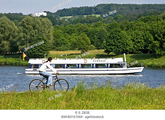 cyclist on the Ruhr-Valley Cycleway at the Kemnade Storage Lake watching the excursion boat `Kemnade¦, Germany, North Rhine-Westphalia, Ruhr Area, Witten