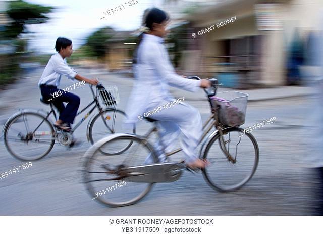 Vietnamese school children cycling to school, Hoi An, Vietnam
