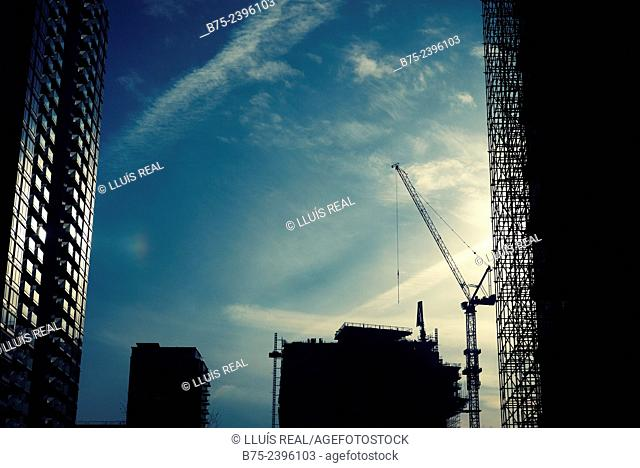Foreground silhouette of the metal structure of a building and a residential building with a crane in South Dock, Docklands, London, England, UK, Europe