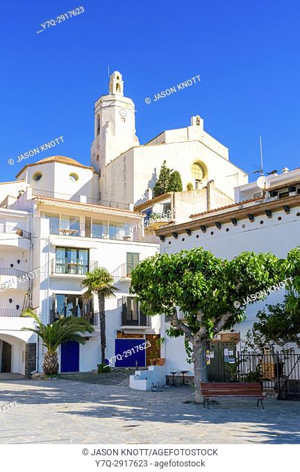 Picturesque whitewashed buildings of Cadaqués Town overlooked by the Santa Maria Church, on the Costa Brava, in the Catalonian region of Spain