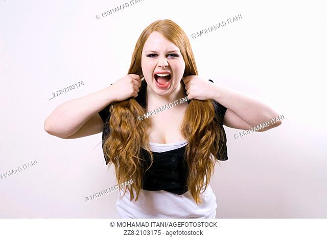 Angry young woman pulling her hair