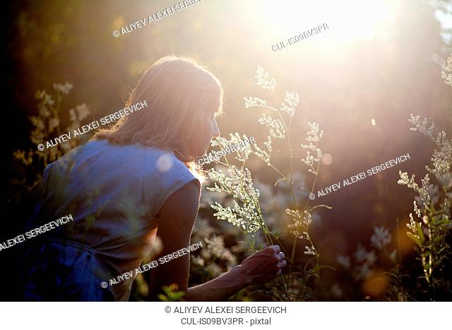 Woman smelling flowers in forest