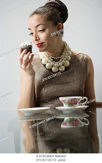 Portrait of a surprised young woman sitting at glass table having breakfast