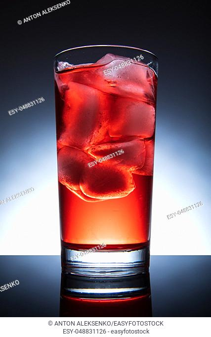 Red cocktail with ice, isolated tall glass