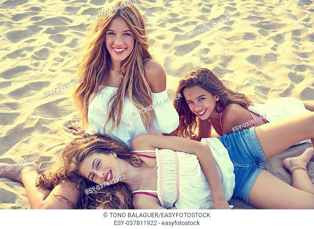 Best friends teen girls together relaxed on a beach sand at sunset