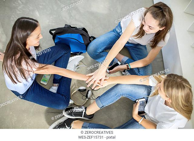 Teenage girls sitting on the floor with cell phones stacking hands