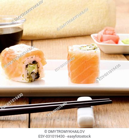 Philadelphia roll sushi on a white plate with soy sauce wasabi and ginger