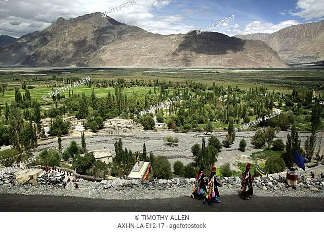 Women in traditional dress walking along road at base of mountains