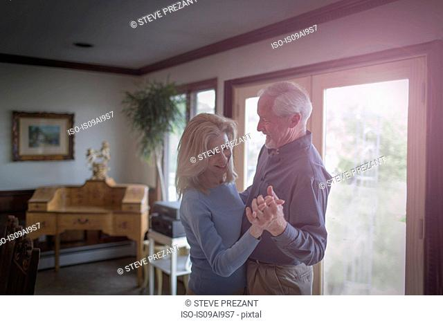 Mature couple waltzing together in dining room