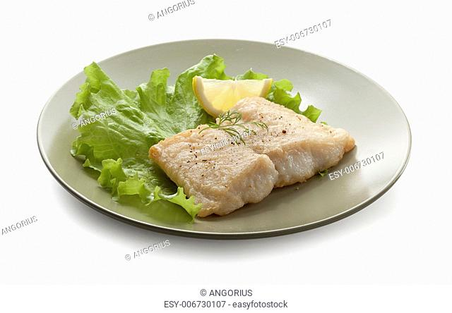 Fried fillet of pangasius with lettuce and lemon on the white plate