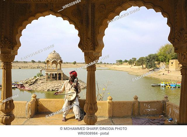 Folk musician playing musical instrument at Gadsisar Gadisar lake , Jaisalmer , Rajasthan , India MR772B