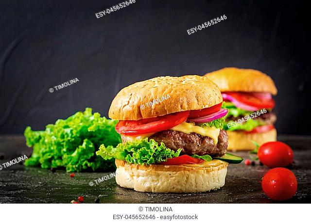 Hamburger with beef meat burger and fresh vegetables on dark background. Tasty food