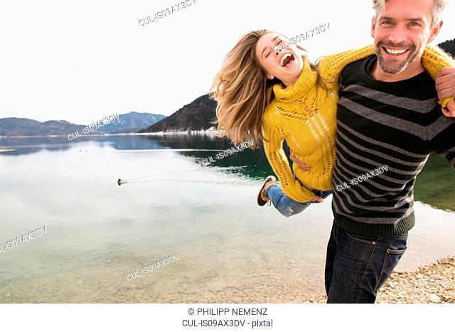 Couple fooling around beside lake, smiling, German Alps, Germany