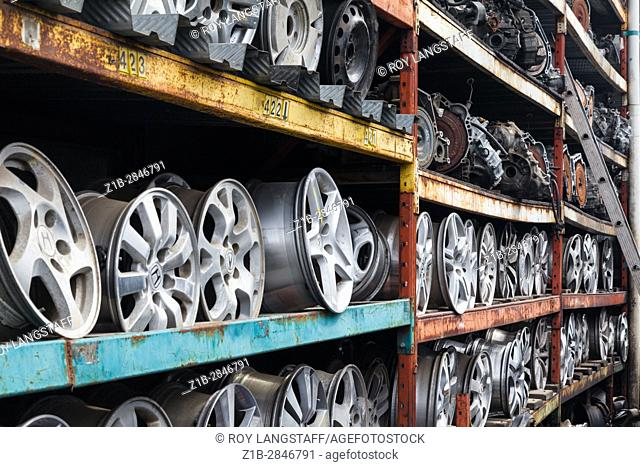 Wheel rims and car transmissions on shelves for resale