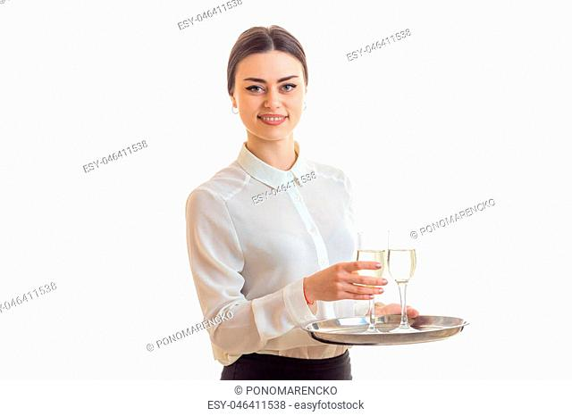 the young waitress smiles and keeps wine glasses on a tray that is isolated on a white background
