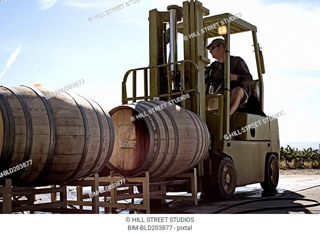 Caucasian farmer driving forklift with barrel