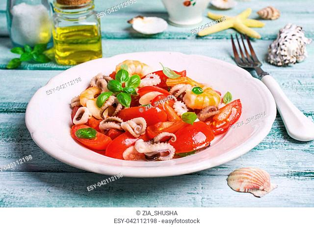 Salad with seafood and vegetables in a plate on the table. Selective focus