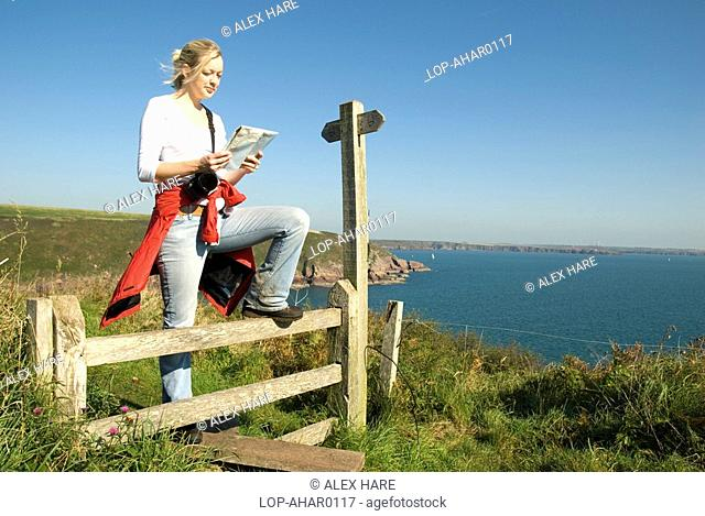 Wales, Pembrokeshire, St Ann's Head, A female walker stops at a stile to read a map above St Ann's Head on the Pembrokeshire coastline