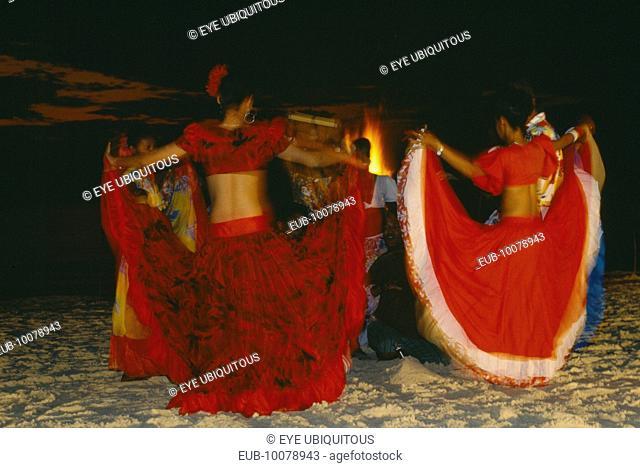 Women in red costume dancing on the beach at night. Sega is the national dance and musical form of Mauritius