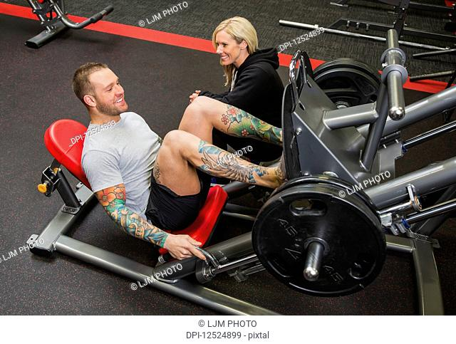 A personal trainer coaching a young man doing leg presses at a fitness facility; Spruce Grove, Alberta, Canada