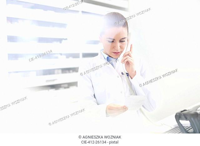 Pharmacist verifying prescription on telephone in pharmacy