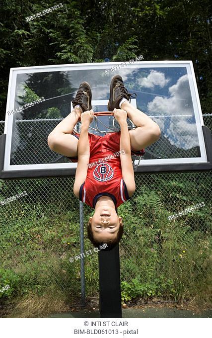 Asian boy hanging upside down on basketball hoop
