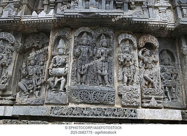 Ornate wall panel reliefs depicting (From left) Shiva-Parvati, a drumer, Lakshmi-Narayana, and other deities Kedareshwara temple, Halebidu, Karnataka, india