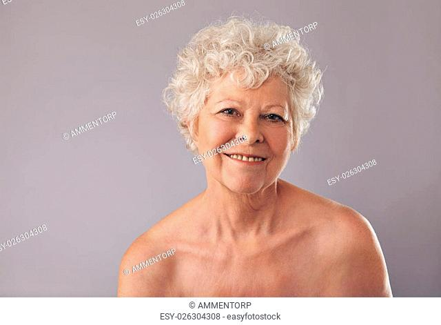 Closeup of an attractive old lady with a sweet smile on her face. Senior woman smiling on grey background