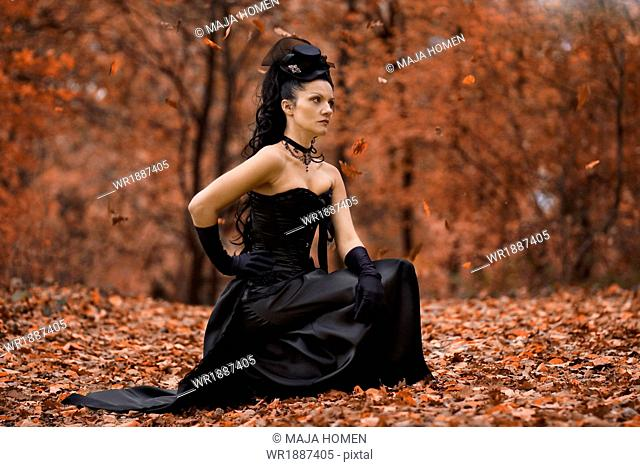 Young woman in Gothic style fashion sits in forest, Croatia, Europe