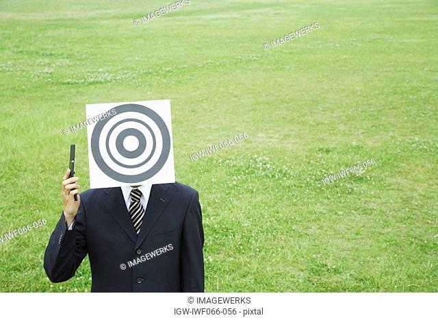 Businessman holding handgun with bull's eye on face
