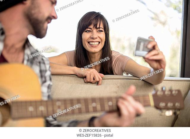 Young man at home playing guitar and woman taking a selfie