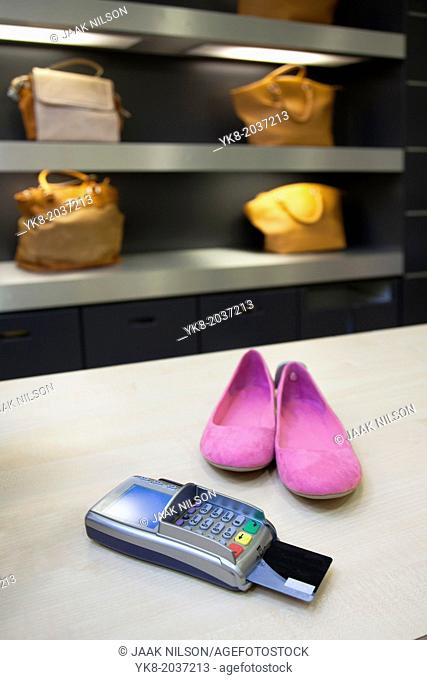 Shoes on clerk desk in retail shop. Card reader and bags or shoulder bags. Pricing, debit machine, counter