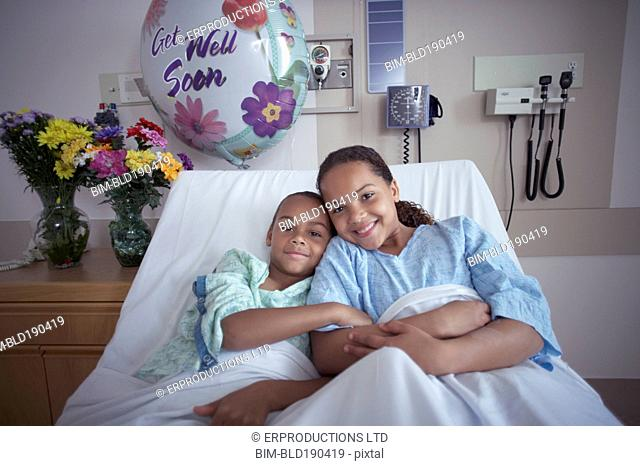 Mixed Race brother and sister in hospital bed