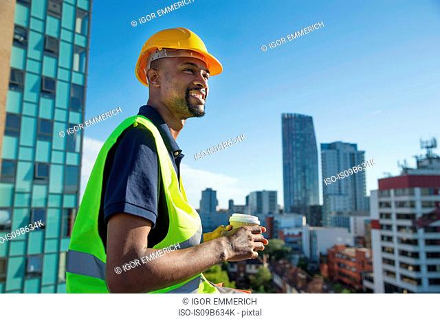 Construction worker outdoors, holding takeaway coffee cup, elevated view of surrounding buildings