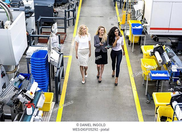 Three smiling women with tablet walking in factory shop floor