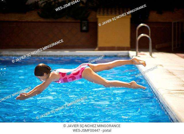 Young girl jumping head first into the pool in summer