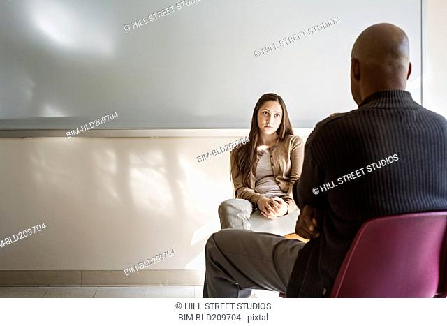 Student and psychologist talking in classroom