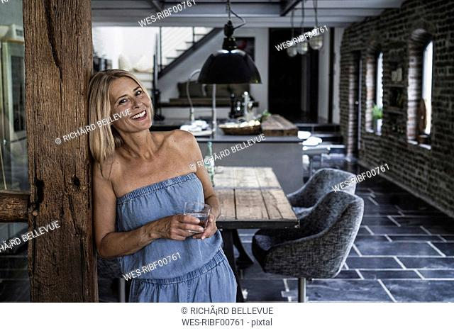 Woman standing in her comfortable country house, smiling