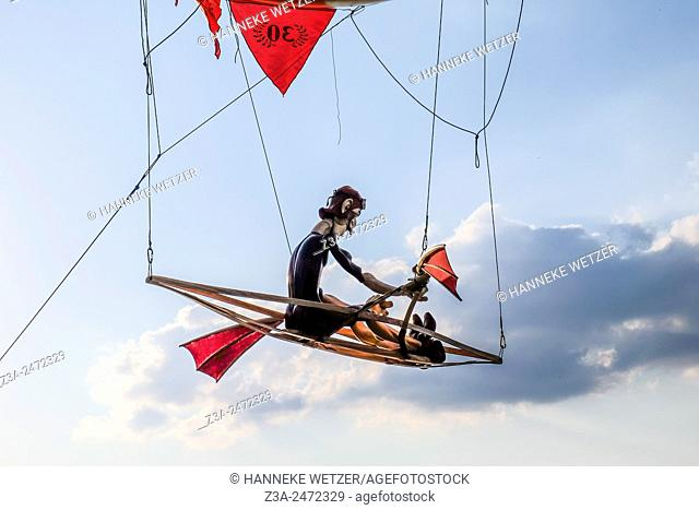 Puppet rowing in a boat under a balloon in the sky