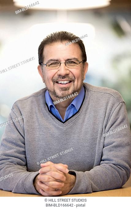 Smiling Hispanic businessman sitting at desk