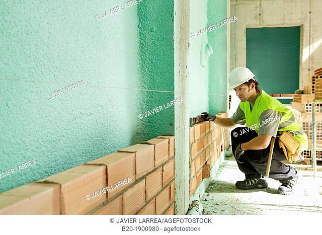 Mason checking the level of a brick wall, Bricklayer with personal protective equipment, PPE, Apartment Building under construction, Donostia, San Sebastian