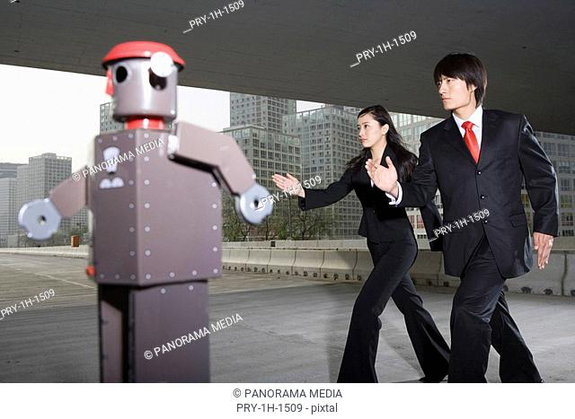 Businessman and woman following robot