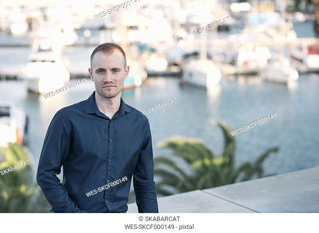 Spain, Barcelona, businessman standing in front of harbour