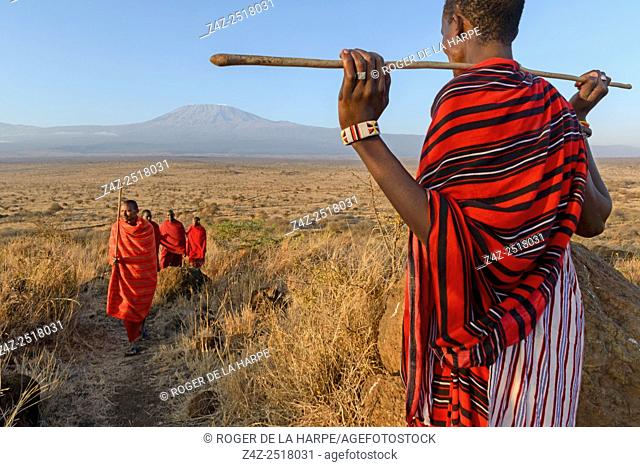 Maasai (Masai) elders with Mount (Mt) Kilimanjaro in the background. Satao Elerai Conservancy. Near Amboseli National Park. Kenya