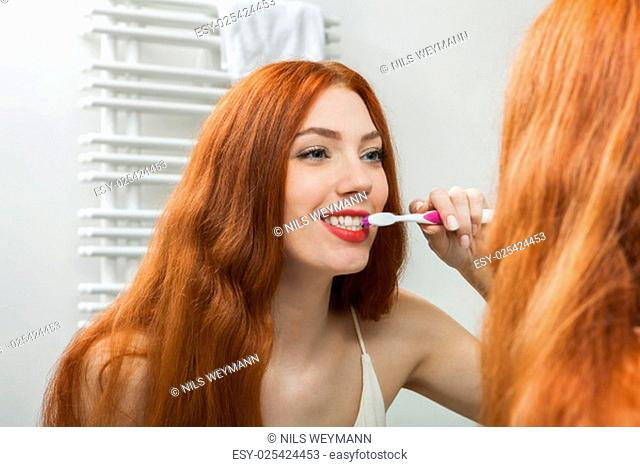 attractive young woman in the morning when brushing your teeth in the mirror in bathroomwith long red hair