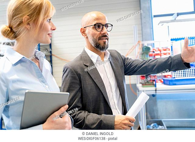 Businessman talking to businesswoman in factory