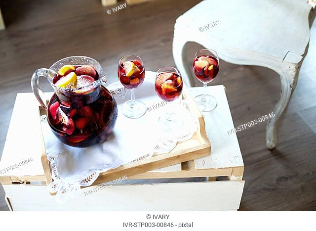 High angle view of jug full of wine and glass in wooden tray placed on table with empty chair